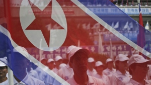 Participants stand behind a North Korean flag at a rally on Liberation Day, the anniversary of the end of the Second World War in 1945 and the Korean Peninsula's liberation from Japanese colonial rule, at the border village of Panmunjom at the DMZ in North Korea on Aug. 15, 2015. (AP / Dita Alangkara)