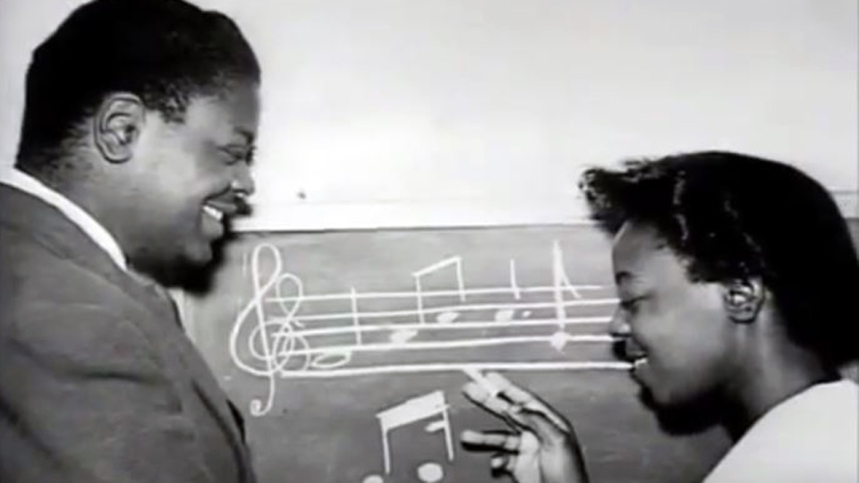Daisy Sweeney and Oscar Peterson at a blackboard