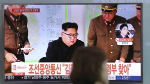 A woman walks by a TV screen showing a local news program reporting about North Korean military's plans to launch missiles into waters near Guam, with an image of North Korean leader Kim Jong Un, at Seoul Train Station in Seoul, South Korea on Tuesday, Aug. 15, 2017. (AP / Lee Jin-man)