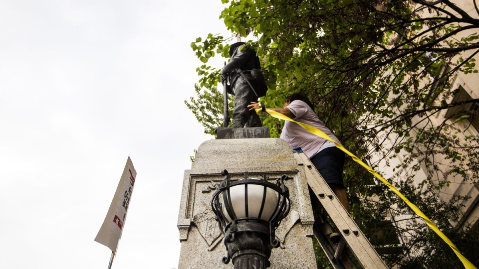An unidentified protester climbs a ladder to place a rope around a Confederate statue during a rally in Durham, N.C., on Aug. 14, 2017. (Casey Toth / The Herald-Sun via AP)