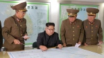 In this Aug. 14, 2017, photo distributed Tuesday, Aug. 15, 2017, by the North Korean government, North Korean leader Kim Jong Un, center, talks with military commanders during his visit to Korean People's Army's Strategic Forces in North Korea.  (Korean Central News Agency/Korea News Service via AP)