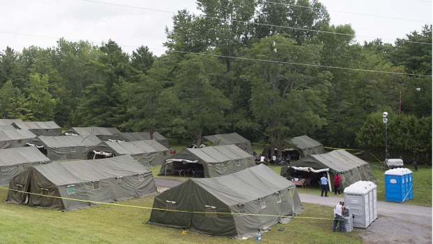 Asylum seekers are shown next to tents at the Canada-United States border in Lacolle, Que. on August 10, 2017. (THE CANADIAN PRESS/Graham Hughes)