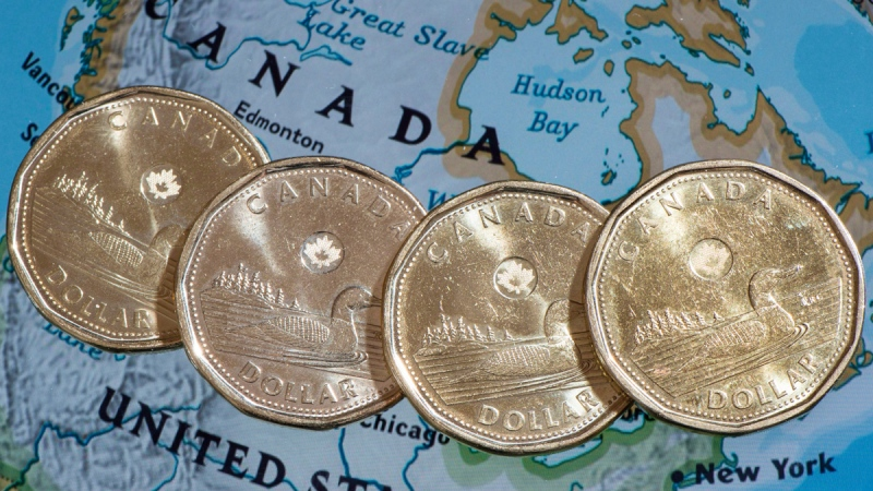 Loonies displayed on a map of North America, on Jan. 9, 2014. (Paul Chiasson / THE CANADIAN PRESS)