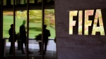 People are reflected in the entrance of the FIFA headquarters in Zurich, Switzerland in this Sept. 24, 2015 file photo. (Walter Bieri/Keystone via AP)