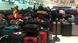A pile of passengers' baggage is shown at Toronto Pearson International Airport after significant technical issues at Terminal 3 departures.