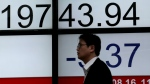 A man walks past an electronic stock indicator of a securities firm in Tokyo on Wednesday, Aug. 16, 2017. (AP / Shizuo Kambayashi)