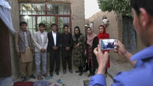 Mohammad Reza Rafat, centre, who received the highest score among thousands of students in this year's university entrance exam, has a photo taken with relatives, following an interview with The Associated Press, in Kabul, Afghanistan on Tuesday, Aug. 1, 2017. (AP / Rahmat Gul)