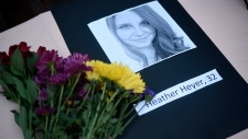 A portrait of Heather Heyer, who was killed when a vehicle drove through counter protesters in Charlottesville, Va., lies on a table with flowers during a vigil on the campus of the University of Southern Mississippi in Hattiesburg, Miss., Monday, Aug 14, 2017. (Courtland Wells / The Vicksburg Post via AP)