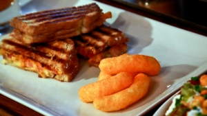 A grilled cheese made with Cheetos is shown during a press preview for a three-day pop-up restaurant featuring an all-Cheetos menu, Tuesday Aug. 15, 2017, in New York. Celebrity chef Anne Burrell has been given the unenviable task of creating an entire menu for a pop-up restaurant based on Cheetos. (AP Photo/Bebeto Matthews)