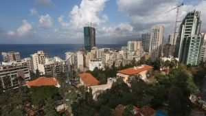 In this February 25, 2014 photo, old buildings with traditional red brick roofs, foreground are overshadowed by newly-constructed modern, tall buildings, in Beirut, Lebanon. (AP Photo/Hussein Malla)