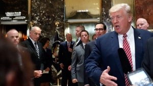 White House chief of staff John Kelly, left, watches as President Donald Trump speaks to the media in the lobby of Trump Tower, Tuesday, Aug. 15, 2017 in Washington. (AP Photo/Pablo Martinez Monsivais)