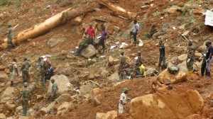 Security forces search for bodies from the scene of heavy flooding and mudslides in Regent, just outside of Sierra Leone's capital Freetown, Tuesday, Aug. 15, 2017. (AP Photo/ Manika Kamara)