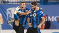 Montreal Impact's Blerim Dzemaili, left, congratulates teammate Ignacio Piatti on his second goal of the game against the Chicago Fire during first half MLS action Wednesday, August 16, 2017 in Montreal. THE CANADIAN PRESS/Paul Chiasson