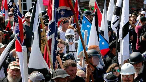White nationalist demonstrators walk into the entrance of Lee Park surrounded by counter demonstrators in Charlottesville, Va., Saturday, Aug. 12, 2017. (Steve Helber/AP Photo)