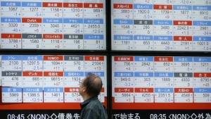 A man looks at an electronic stock board showing Japan's Nikkei 225 index at a securities firm in Tokyo on Thursday, Aug. 17, 2017. (AP / Eugene Hoshiko)