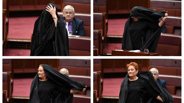 In this combination of photos Sen. Pauline Hanson takes off a burqa she wore into the Senate chamber at Parliament House in Canberra, Australia on Thursday, Aug. 17, 2017. (Lukas Coch / AAP Image)