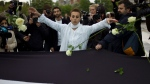In this April 17, 2012 file photo, Syrian actress and activist, Fadwa Suleiman, centre, throws roses on a giant Syrian flag during the 'White Wave' campaign to protest against the violence in Syria, in Paris. (AP Photo/Thibault Camus, File)