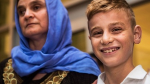 Nofa Mihlo Rafo, left, is reunited with her 12-year-old son Emad Mishko Tamo at Winnipeg's James Armstrong Richardson International Airport Thursday August 17, 2017. Emad Mishko Tamo was rescued by Iraqi forces in July, after being held captive by ISIL for the past three years. THE CANADIAN PRESS/David Lipnowski