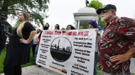 Members of the Take Em Down Jax organization hold a banner with the list of offending confederate monuments as well as buildings and locations they want renamed during a rally in Jacksonville's Confederate Park in Jacksonville, Fla, Tuesday, Aug 15, 2017. Several organizations wanting the removal of confederate monuments and have the names changed on schools and bridges met at the base of the Woman of the Southland statue in Confederate Park North of downtown Jacksonville. Roughly 30 demonstrators against the monuments and around 10 who wanted them left alone were kept in check with the presence of around a dozen members of the Jacksonville Sheriffs Office. (Bob Self/The Florida Times-Union via AP)
