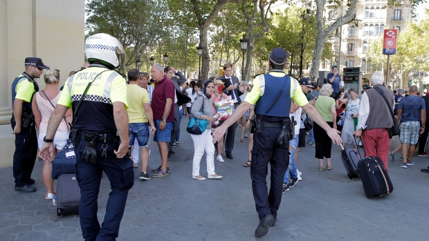 Police officers tell members of the public to leave the scene in a street in Barcelona, Spain, Thursday, Aug. 17, 2017. (AP Photo/Manu Fernandez)