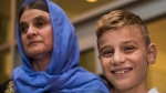 Nofa Mihlo Rafo, left, is reunited with her 12-year-old son Emad Mishko Tamo at Winnipeg's James Armstrong Richardson International Airport August 17, 2017. (David Lipnowski/THE CANADIAN PRESS)