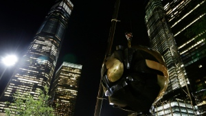 A section of the Koenig Sphere, a 25-ton bronze sphere damaged by the collapsing World Trade Center is lifted by crane into Liberty Park near One World Trade Center on Wednesday, Aug. 16, 2017, in New York. The sphere once stood between the trade center's two towers. (AP / Peter Morgan)