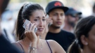 People speak on their phones as they stand on a street in Barcelona, Spain, Thursday, Aug. 17, 2017. Police in the northern Spanish city of Barcelona say a white van has jumped the sidewalk in the city's historic Las Ramblas district, injuring several people. (AP Photo/Manu Fernandez)