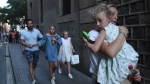 People flee the scene in Barcelona, Spain, Thursday, Aug. 17, 2017 after a white van jumped the sidewalk in the historic Las Ramblas district, crashing into a summer crowd of residents and tourists and injuring several people, police said. (AP Photo/Giannis Papanikos)