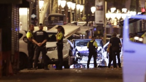 Police officers stand next to the van involved on an attack in La Rablas in Barcelona, Spain, on Aug. 17, 2017. (Manu Fernandez / AP)