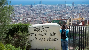 A tourist takes a picture of the city's panorama as he stands next to a wall with a graffito reading 'Tourist: your luxury trip - my daily misery' at Park Guell, in Barcelona, on Aug. 10, 2017. (Josep LAGO / AFP)