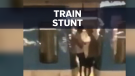 Pair rides on the outside of subway train