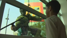 A child and the Incredible Hulk stand on opposite sides of a hospital window