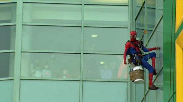 A group of children watch as Spiderman cleans the windows of the Alberta Children's Hospital