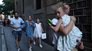People flee the scene after a white van jumped the sidewalk in the historic Las Ramblas district, crashing into a summer crowd of residents and tourists and injuring several people, police said, in Barcelona, Spain, Thursday, August 17, 2017. (AP Photo/Giannis Papanikos)