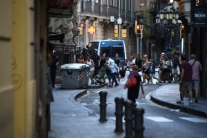 People flee the scene as police officers patrols after a white van jumped the sidewalk in the historic Las Ramblas district in Barcelona, Spain, Thursday, August 17, 2017. (AP Photo/Giannis Papanikos)