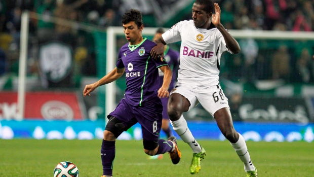 Sporting's Andre Martins, left, duels for the ball with Nacional's Aly Ahmed Ghazal, from Egypt, during the Portuguese league soccer match between Sporting and Nacional at the Alvalade stadium in Lisbon, Saturday, Dec. 21, 2013. (Francisco Seco / THE CANADIAN PRESS)