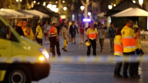Emergency workers stand on a blocked street in Barcelona, Spain, Thursday, Aug. 17, 2017. A white van jumped up onto a sidewalk and sped down a pedestrian zone Thursday in Barcelona's historic Las Ramblas district, swerving from side to side as it plowed into tourists and residents. Police said 13 people were killed and more than 50 wounded in what they called a terror attack. (AP Photo/Manu Fernandez)