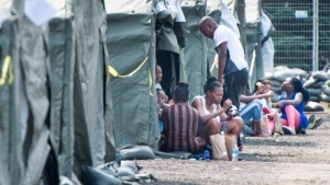 Asylum seekers sit in front of their tent in a temporary camp, Tuesday, August 15, 2017 near Saint-Bernard-de-Lacolle, Que. The camp was set up to cope with the crush of asylum seekerscrossing into Canada from the United States. THE CANADIAN PRESS/Paul Chiasson
