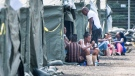 Asylum seekers sit in front of their tent in a temporary camp near Saint-Bernard-de-Lacolle, Que. on Tues., Aug. 15, 2017. (Paul Chiasson / THE CANADIAN PRESS)