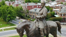 FILE - This Tuesday, June 27, 2017 photo shows the statue of Confederate Gen. Robert E. Leethat stands in the middle of a traffic circle on Monument Avenue in Richmond, Va. As cities across the United States are removing Confederate statues and other symbols, dispensing with what some see as offensive artifacts of a shameful past marked by racism and slavery, Richmond is taking a go-slow approach. (AP Photo/Steve Helber)