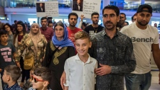 12-year-old Emad Mishko Tamo, centre, stands with uncle Hadji Tamo and his mother Nofa Mihlo Rafo as he's reunited with friends and family at Winnipeg's James Armstrong Richardson International Airport, early Thursday, August 17, 2017. Emad Mishko Tamo was rescued by Iraqi forces in July, after being held captive by ISIL for the past three years. THE CANADIAN PRESS/David Lipnowski