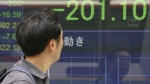 A man looks at an electronic stock board of a securities firm in Tokyo on Friday, Aug. 18, 2017. (AP / Koji Sasahara)