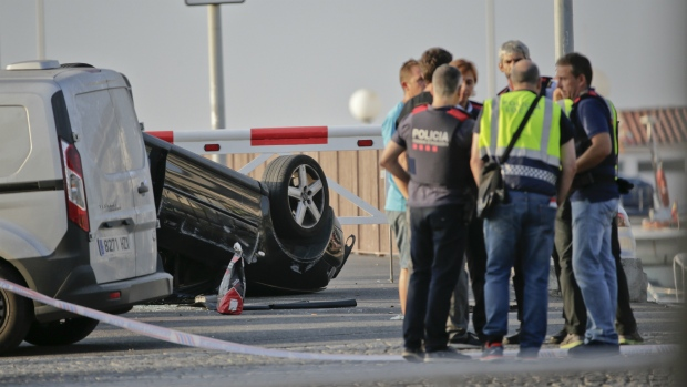 Police officers speak near an overturned car at the spot where terrorists were intercepted by police in Cambrils, Spain, Friday, Aug. 18, 2017. (AP / Emilio Morenatti)