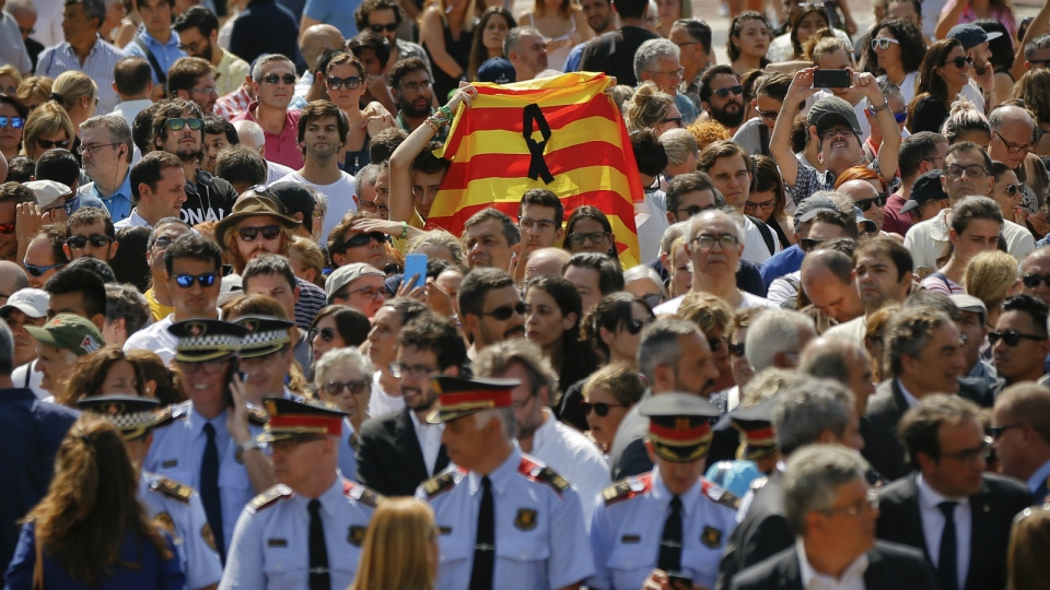 People holding a Catalan flag gather for a minute of silence in memory of the terrorist attacks victims in Las Ramblas, Barcelona, Spain on Friday, Aug. 18, 2017. (AP / Francisco Seco)