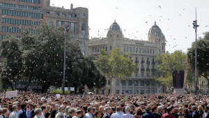 Pigeons fly as people gather for a minute of silence in memory of the terrorist attacks victims in Las Ramblas, Barcelona, Spain, Friday, Aug. 18, 2017. (AP Photo/Manu Fernandez)