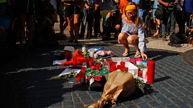 A woman places a postcard of the Barcelona's Sacred Family cathedral next to bunches of flowers in Las Ramblas, Barcelona, Spain, Friday, Aug. 18, 2017. Police on Friday shot and killed five people carrying bomb belts who were connected to the Barcelona van attack, as the manhunt intensified for the perpetrators of Europe's latest rampage claimed by the Islamic State group. (AP Photo/Francisco Seco)