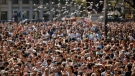 Pigeons fly over crowds gathered for a minute of silence in memory of the terrorist attacks victims in Las Ramblas, Barcelona, Spain, Friday, Aug. 18, 2017. (AP Photo/Francisco Seco)