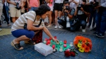 "A woman places a candle on a paper that reads ""Catalunya - place of peace"" in Las Ramblas, Barcelona, Spain, Friday, Aug. 18, 2017. (AP Photo/Manu Fernandez)"
