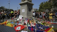 People look at flags, messages and candles placed after van attack in central Barcelona, Spain, on Aug. 18, 2017. (Manu Fernandez / AP)