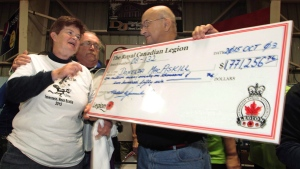 Donelda MacAskill, 62, of Englistown, N.S., receives a cheque for more than $1.7 million after flipping over the ace of spades in the final Chase the Ace draw in Inverness, Nova Scotia on Saturday Oct. 4, 2015. (Darren Pittman/The Canadian Press)